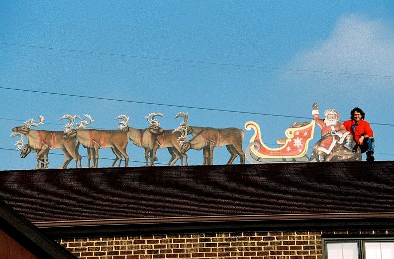Poses with his santa sleigh and reindeer on a suburban rooftop 1992